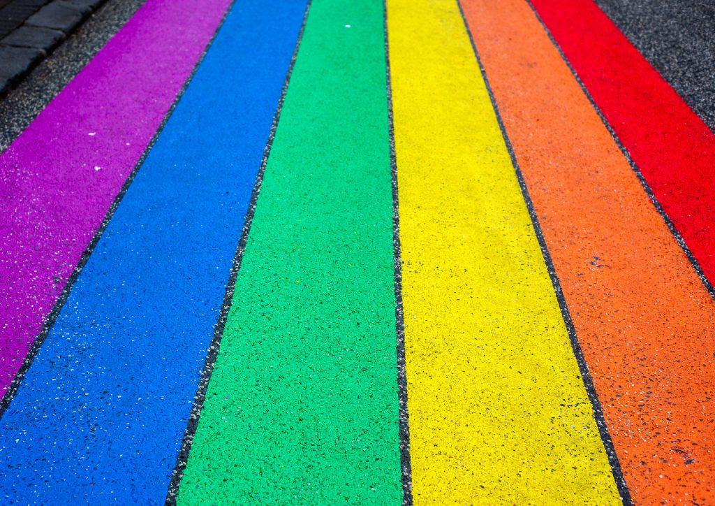 Eine Straße mit aufgemalten Streifen in Regenbogenfarben