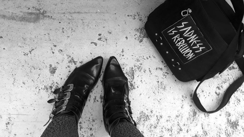 """Pikes und eine Tasche mit der Aufschrift """"Sadness is rebellion"""""""